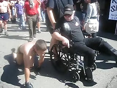 Man in wheelchair has a pet male human at Folsom Fair